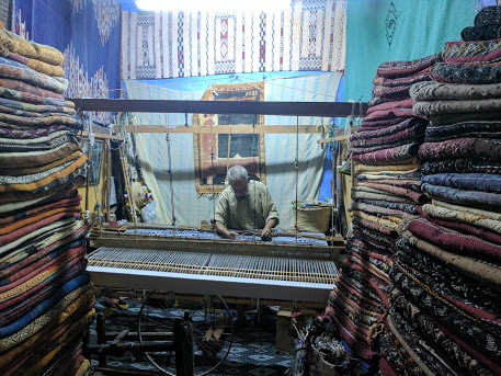 Moroccan man weaving rug in one of the shops